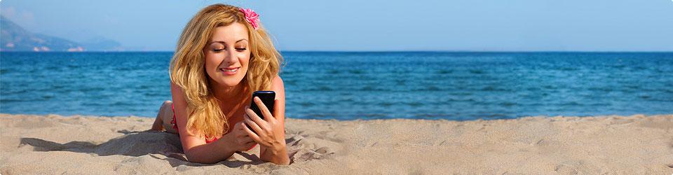 Junge Frau liegt am Strand und schaut auf ihr Handy.